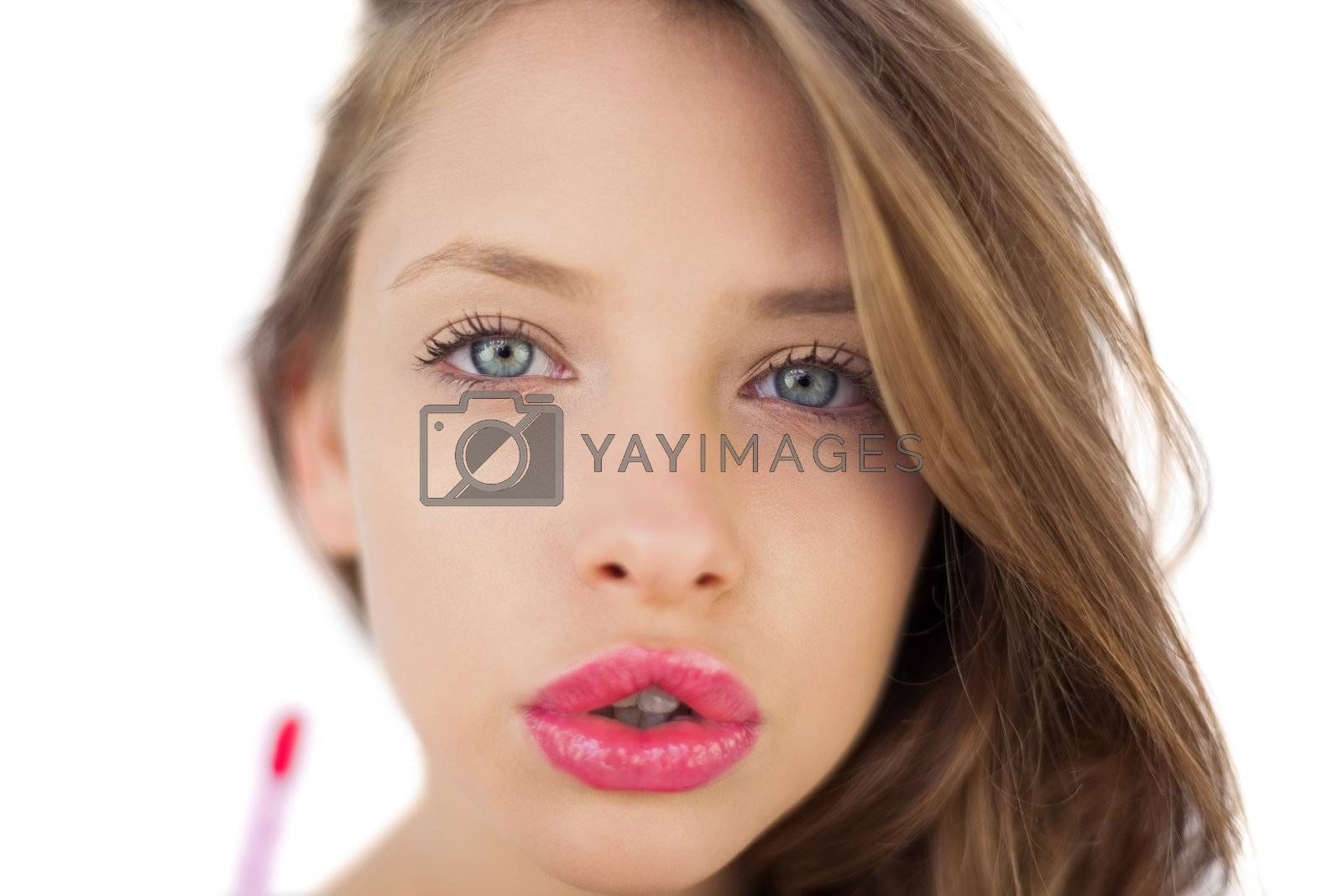 Concentrated brunette model applying pink gloss by Wavebreakmedia