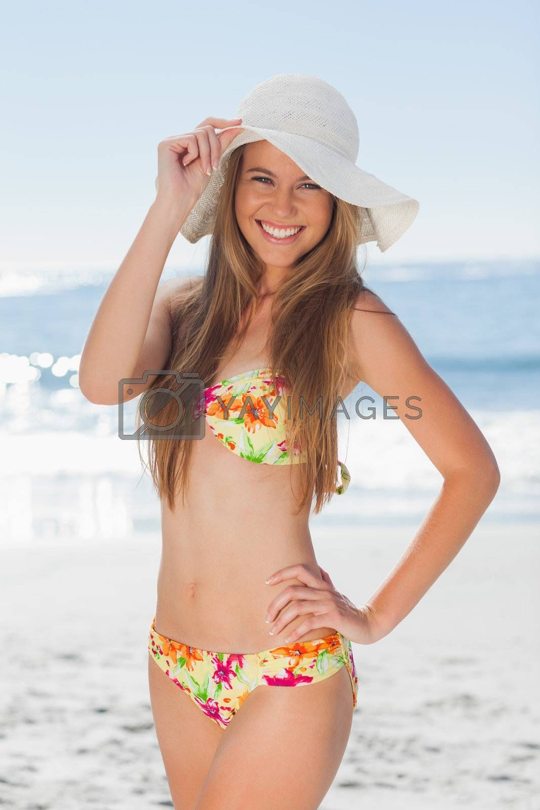 Young smiling woman in bikini standing with her hand on her hip by Wavebreakmedia