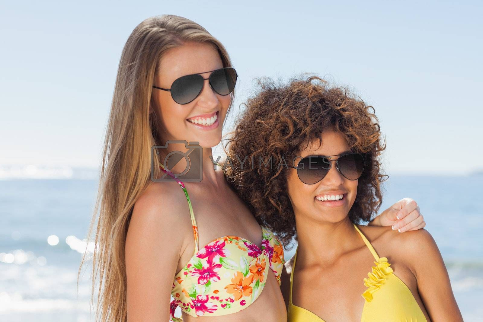 Two friends wearing sunglasses on the beach and smiling by Wavebreakmedia