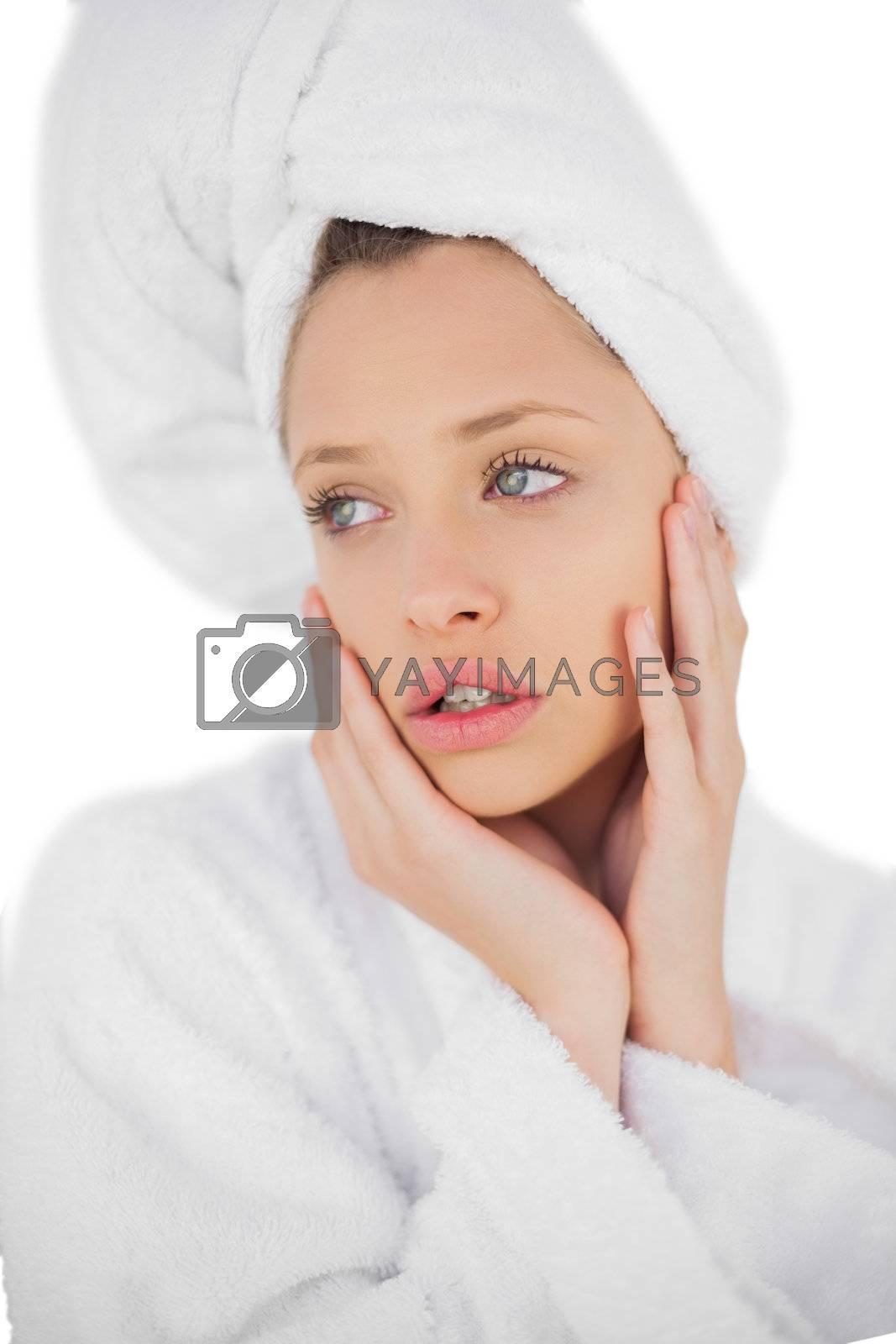 Anxious brunette in bathrobe looking away by Wavebreakmedia