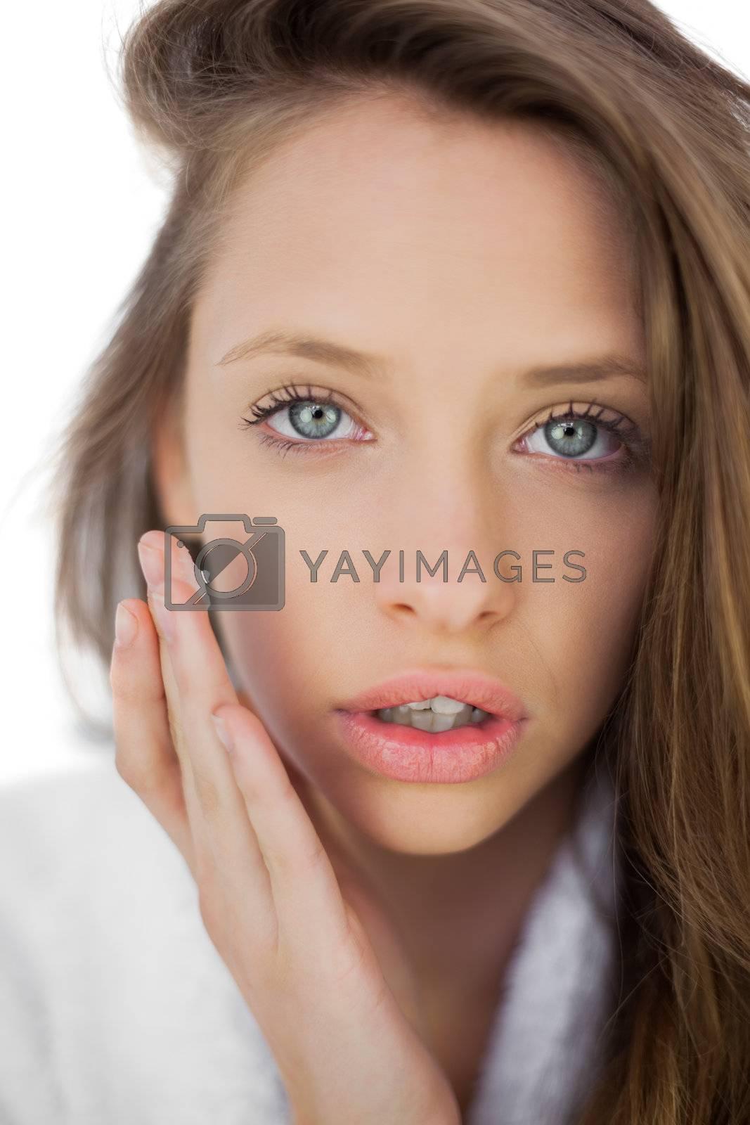 Pensive brunette in bathrobe rubbing her cheek with cream by Wavebreakmedia