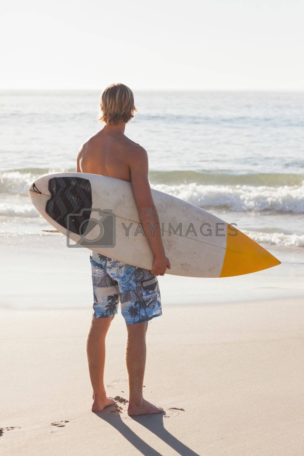 Man with his surfboard on the beach by Wavebreakmedia