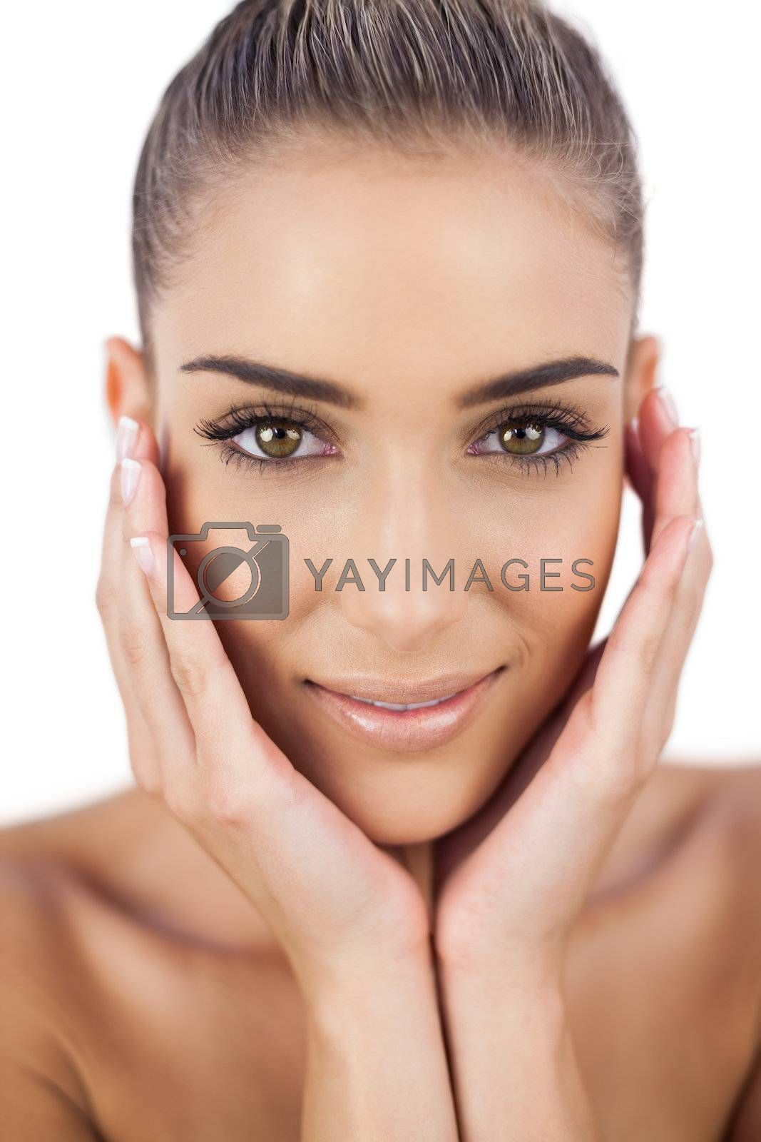 Nice woman holding her head and looking at camera by Wavebreakmedia