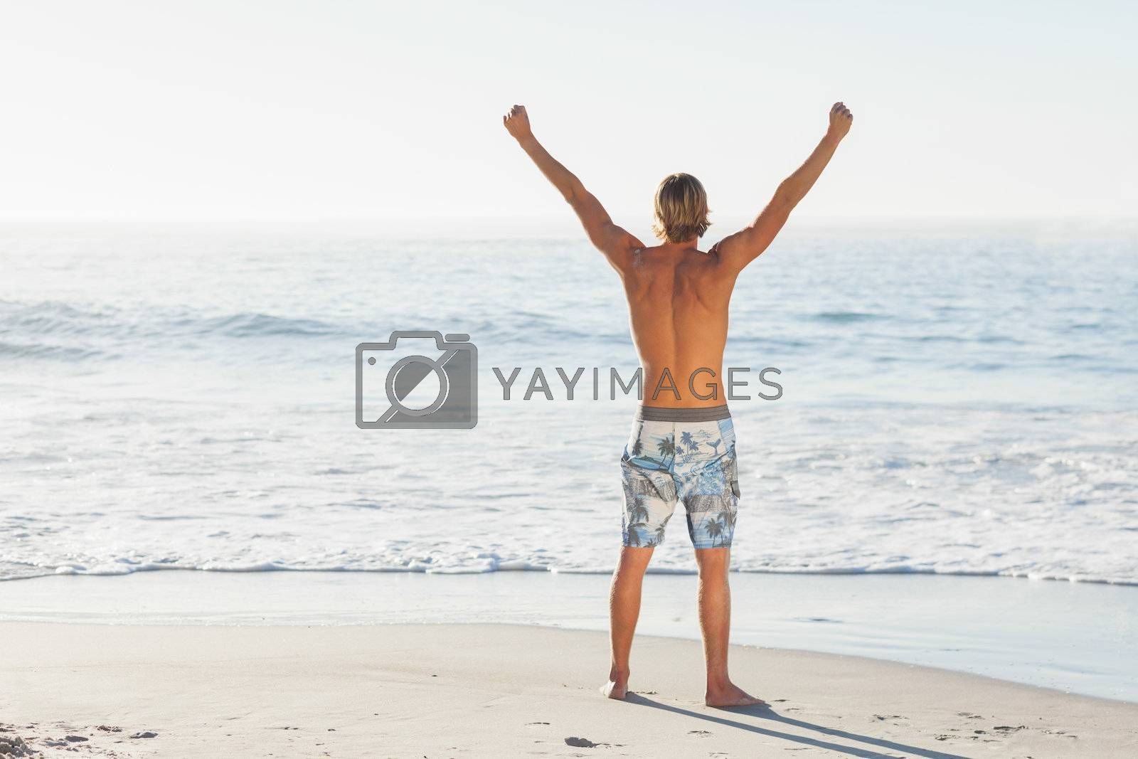 Man cheering looking out to the sea by Wavebreakmedia
