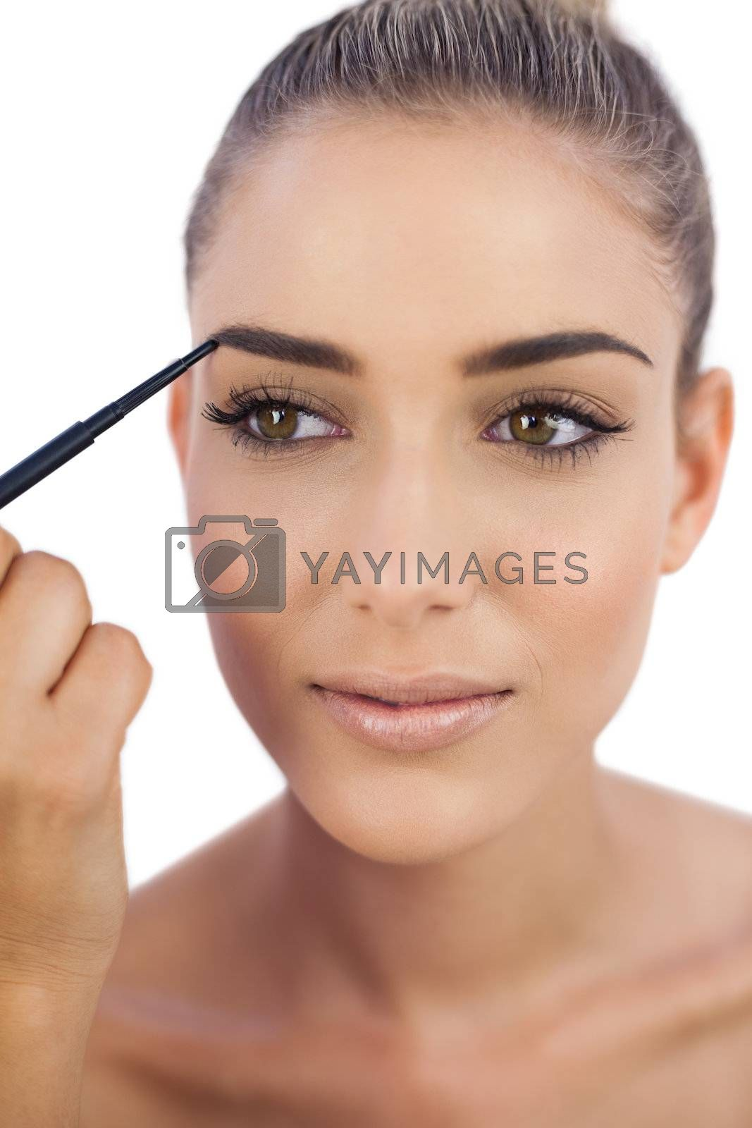 Smiling woman applying make up on her eyebrows by Wavebreakmedia