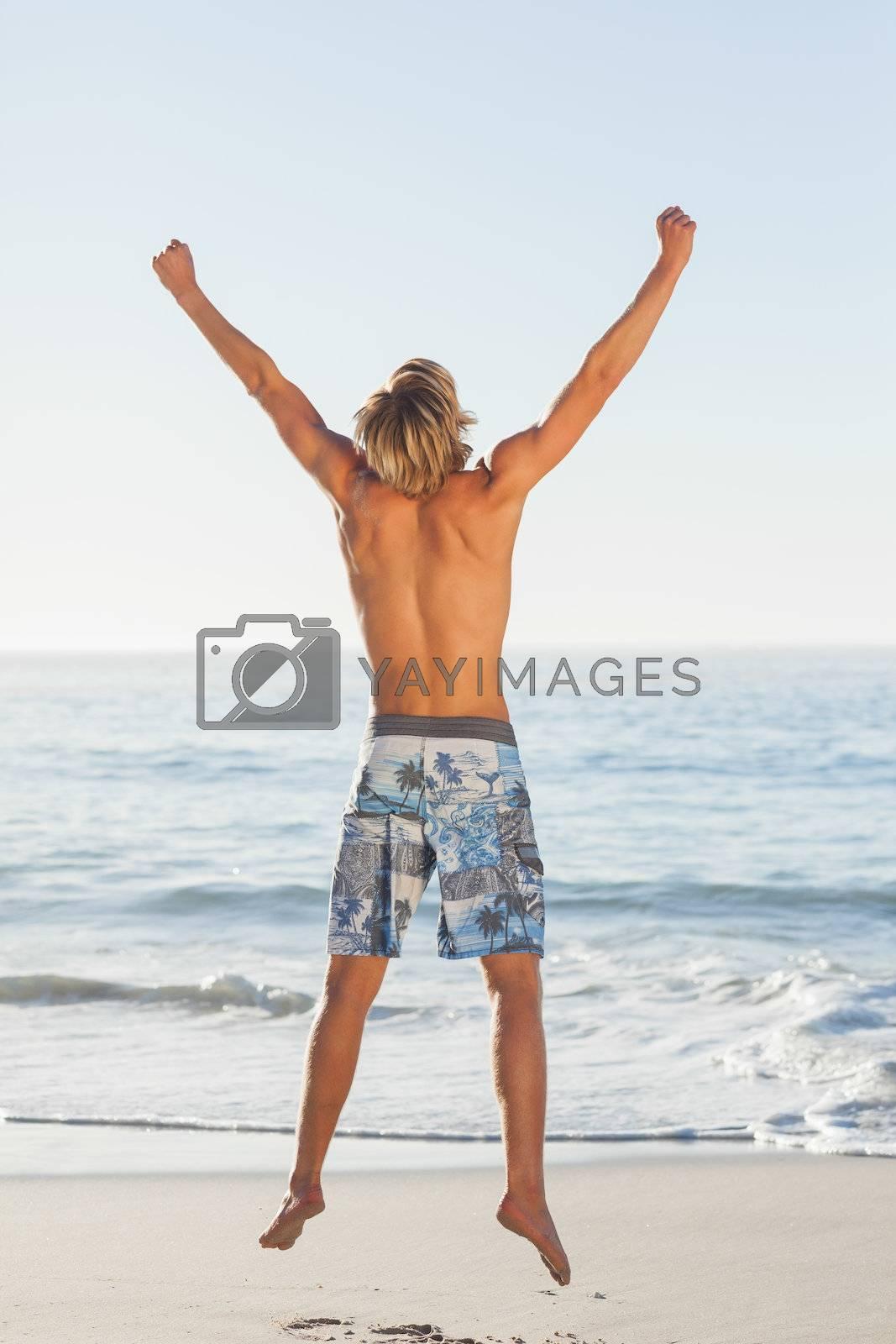 Blonde man jumping by Wavebreakmedia