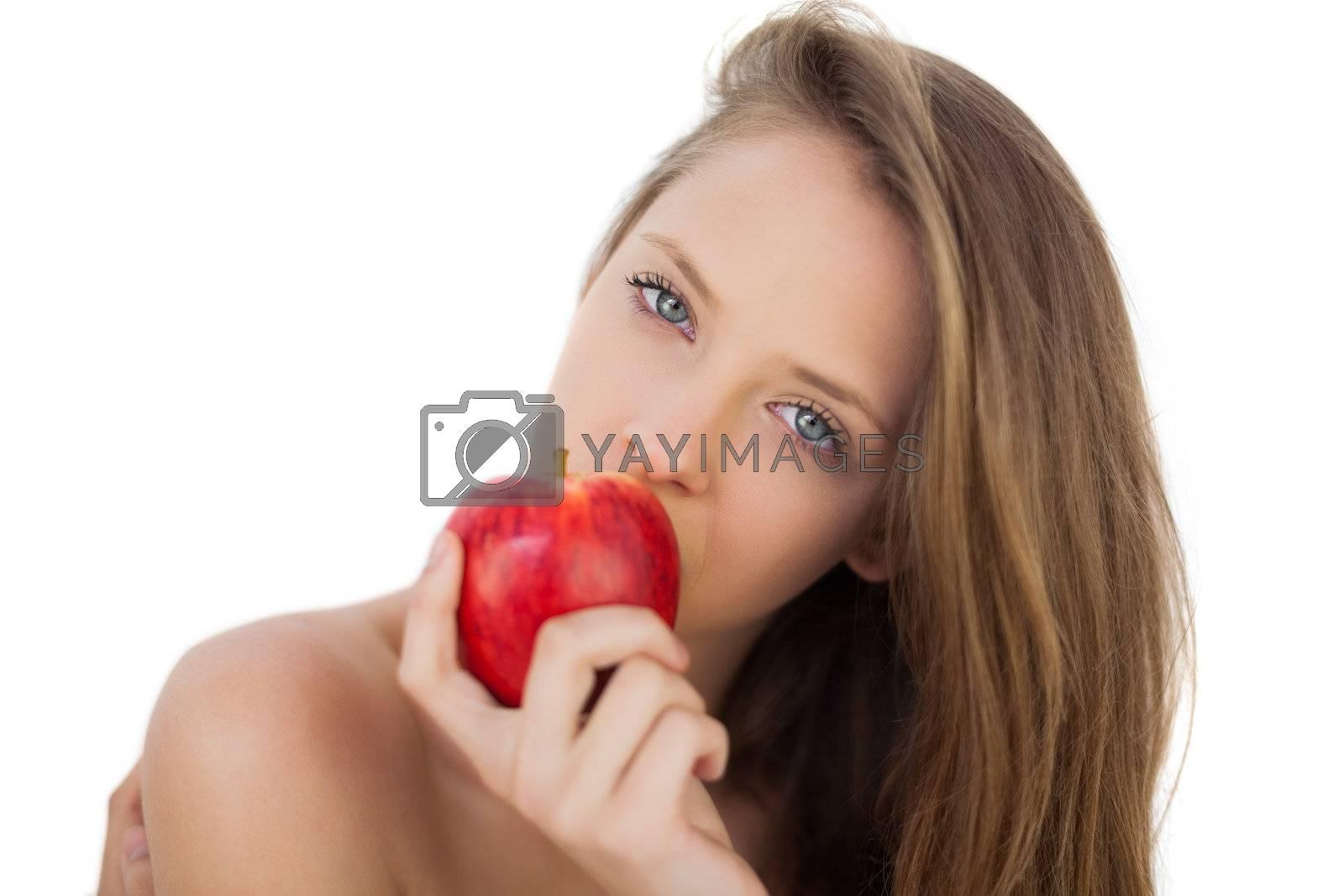 Pensive brunette model eating an apple by Wavebreakmedia