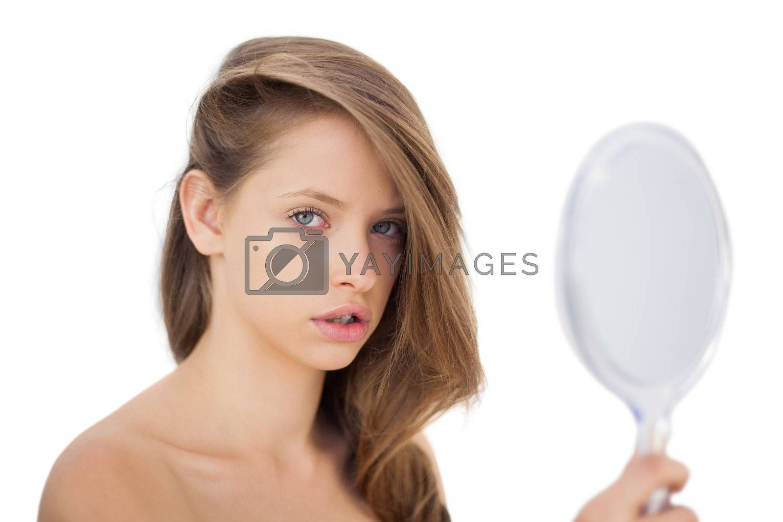 Attentive brunette model posing holding a mirror by Wavebreakmedia
