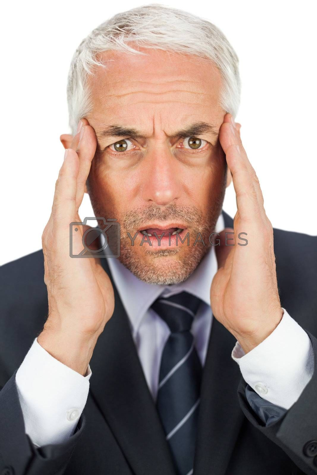 Surprised businessman looking at camera holding his temples by Wavebreakmedia