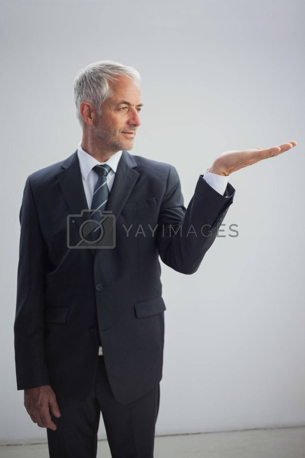 Unsmiling businessman presenting something by Wavebreakmedia