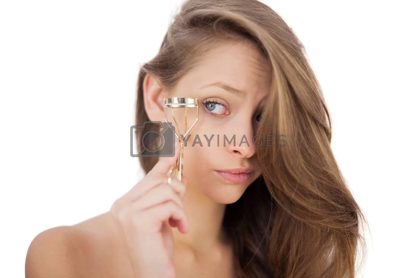 Puzzled brunette model looking an eyelash curler by Wavebreakmedia