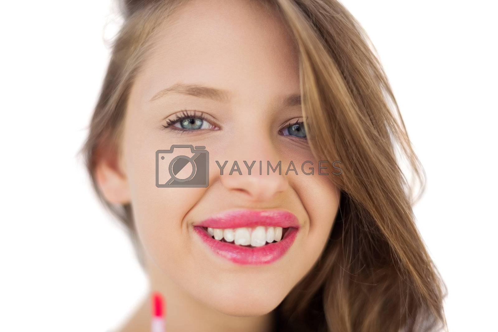 Happy brunette girl holding a gloss tube by Wavebreakmedia