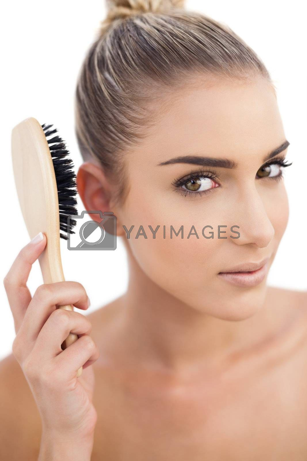 Thoughtful brunette holding a hairbrush by Wavebreakmedia