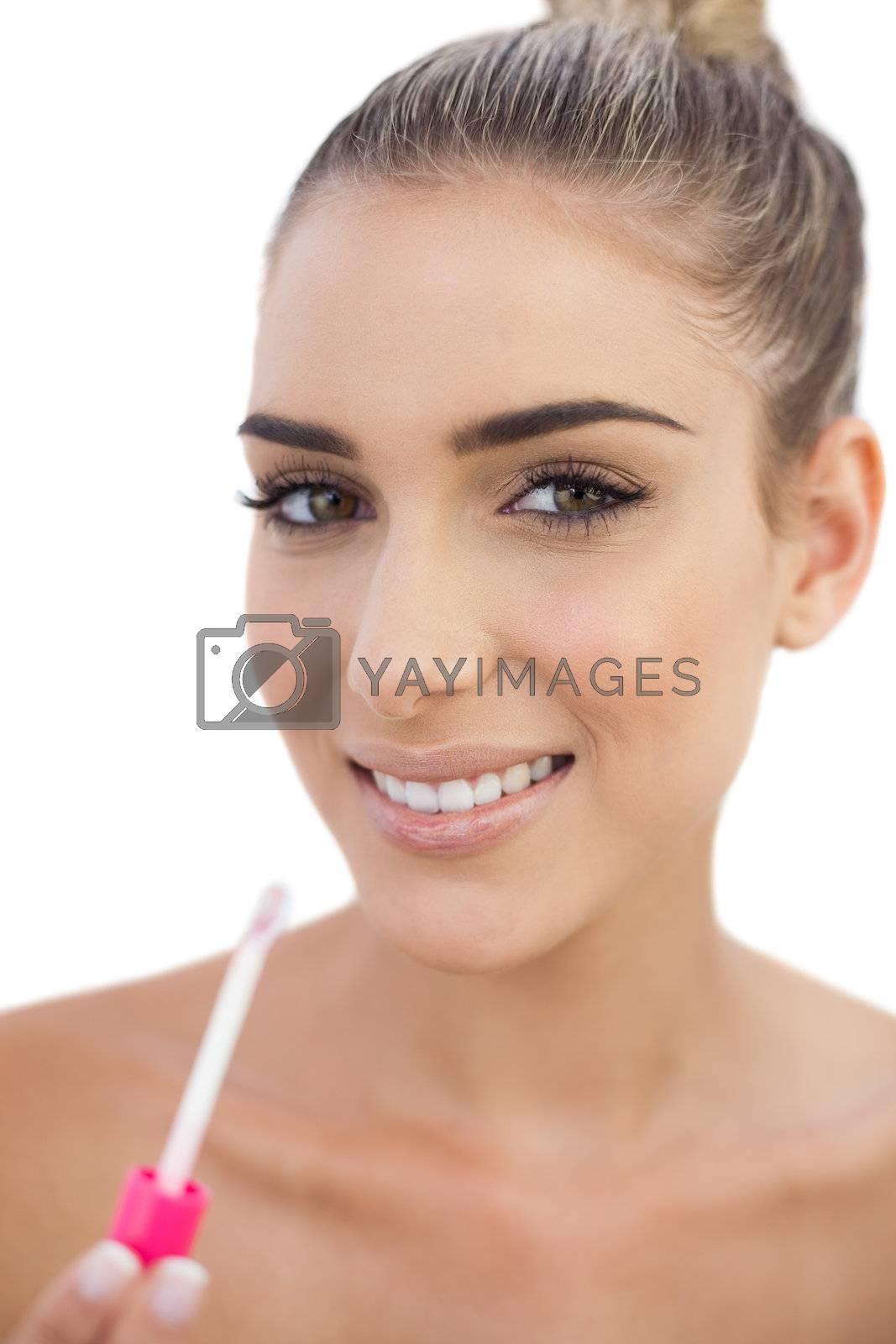 Cheerful woman applying gloss on her lips by Wavebreakmedia