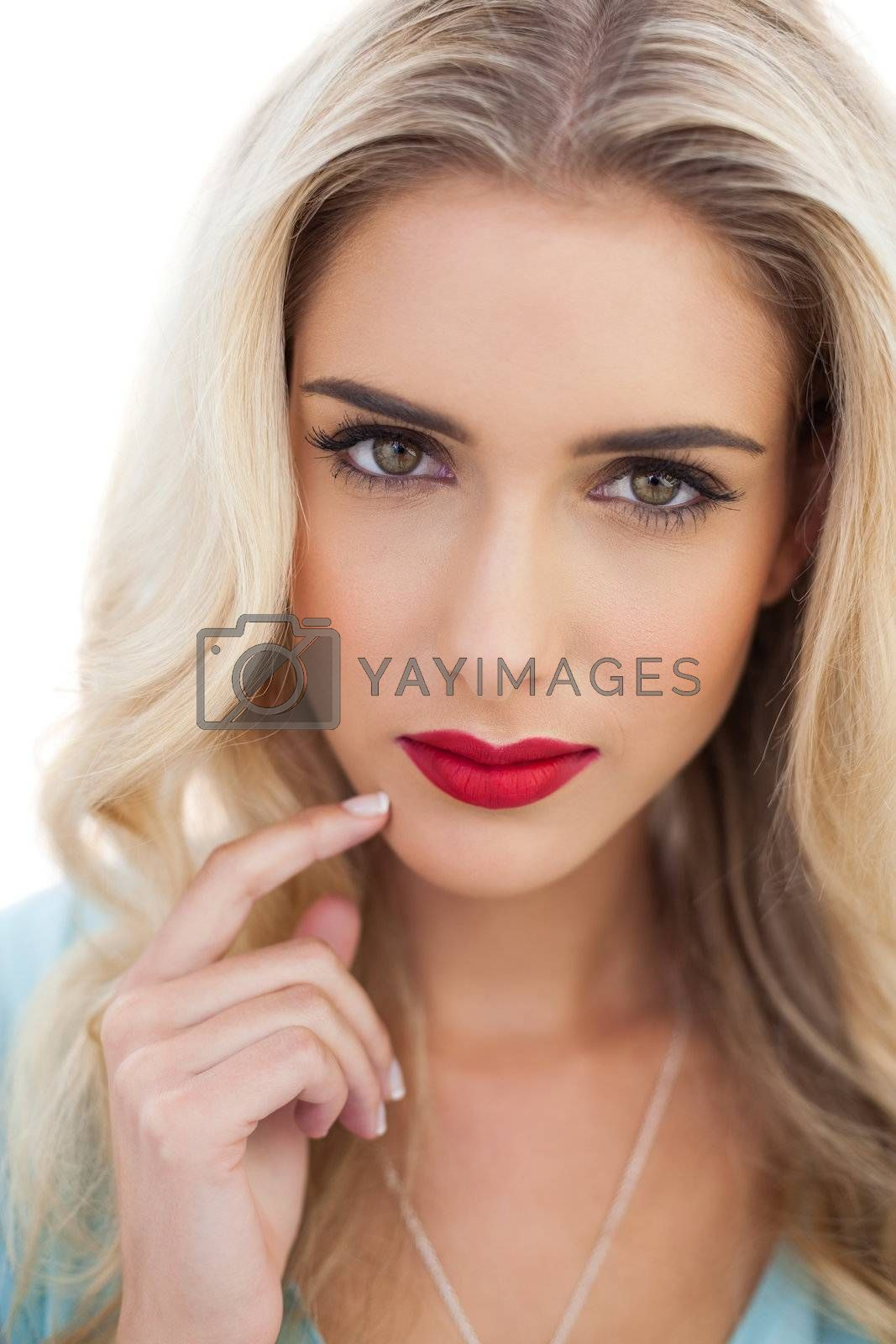 Portrait of a pensive blonde woman in blue dress looking at camera by Wavebreakmedia