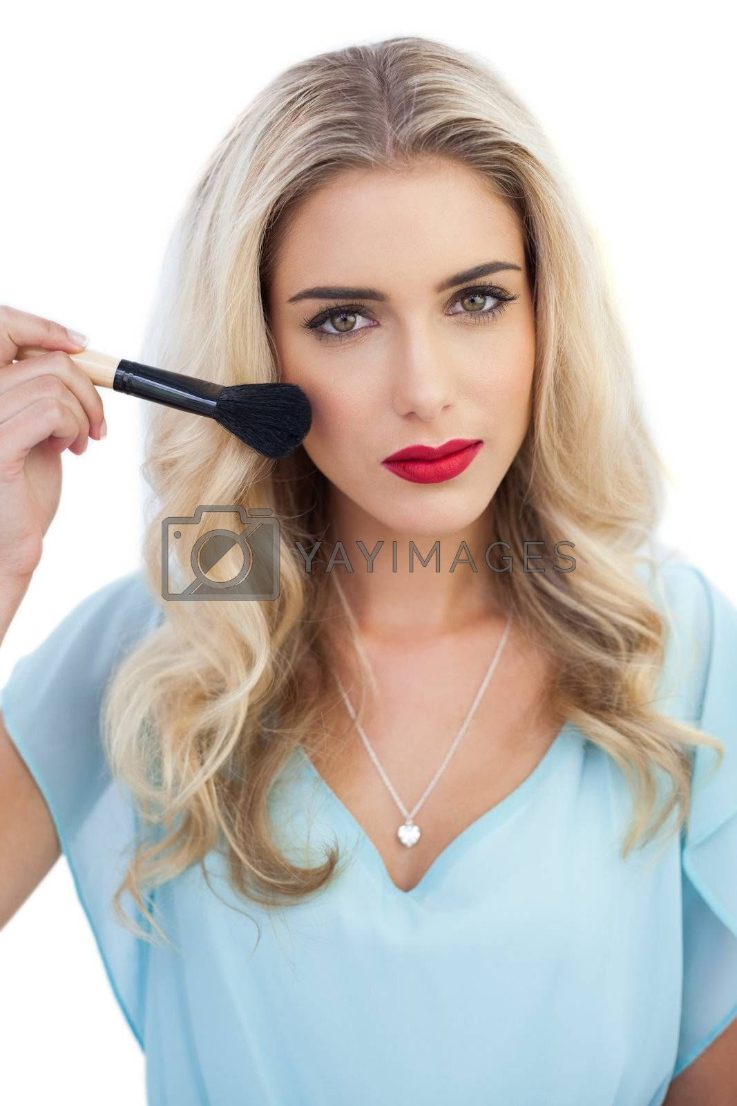 Serious blonde model in blue dress applying make up by Wavebreakmedia