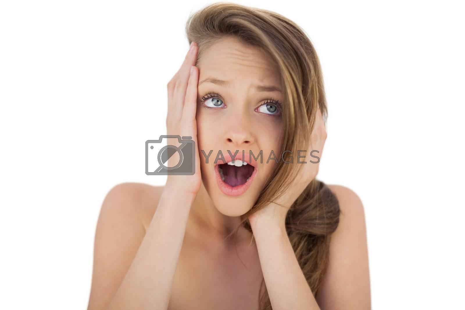 Shocked brunette model holding her head by Wavebreakmedia