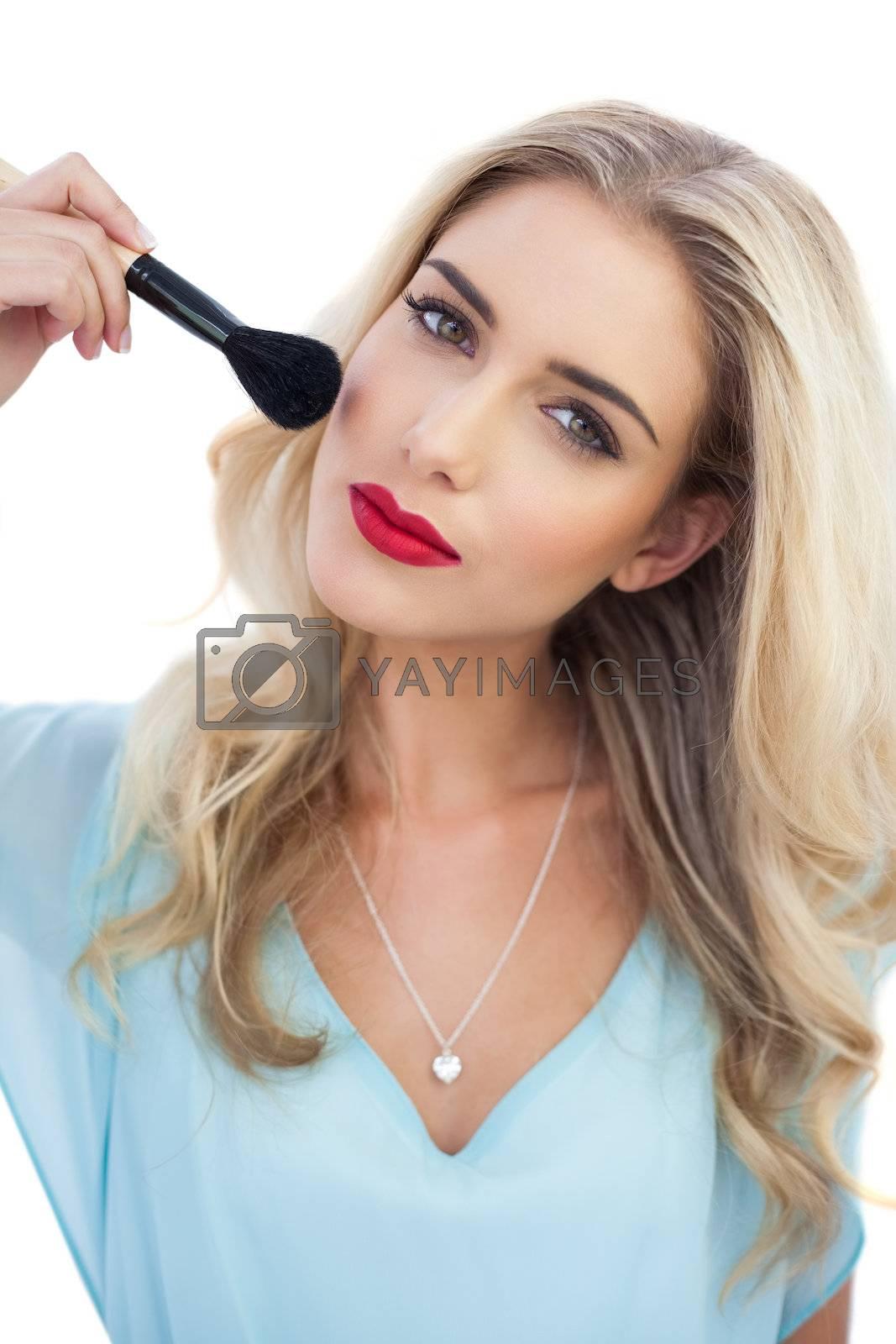 Thoughtful blonde model in blue dress applying make up by Wavebreakmedia