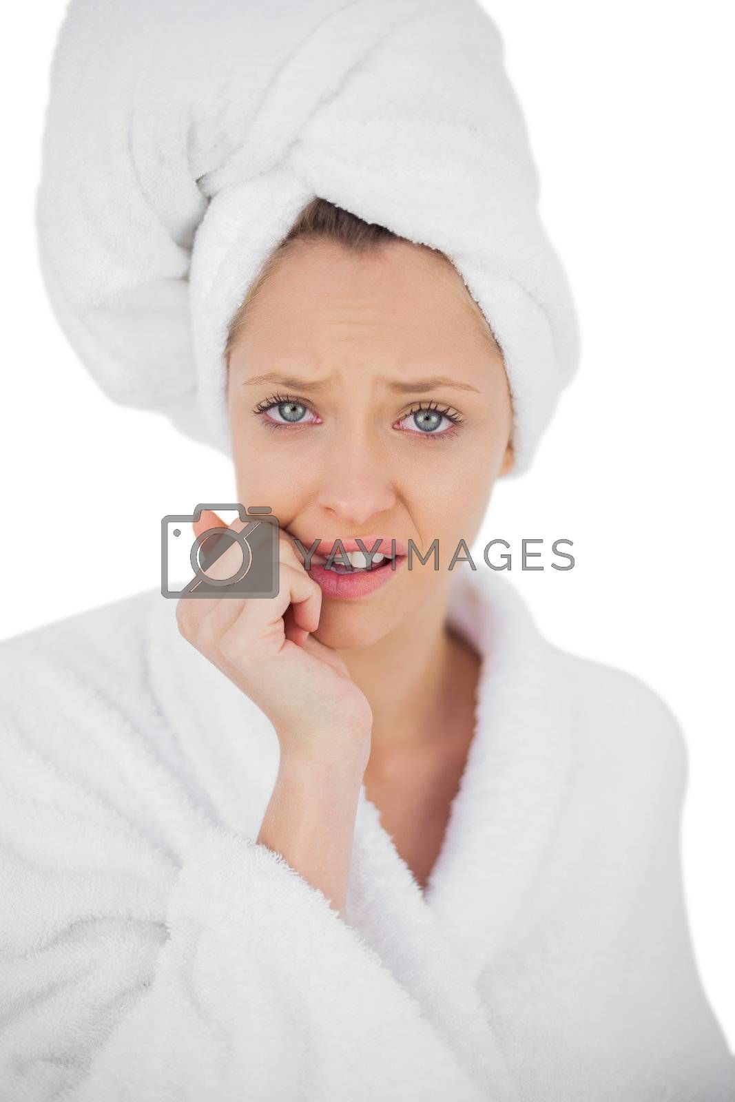 Worried brunette in bathrobe looking at camera by Wavebreakmedia