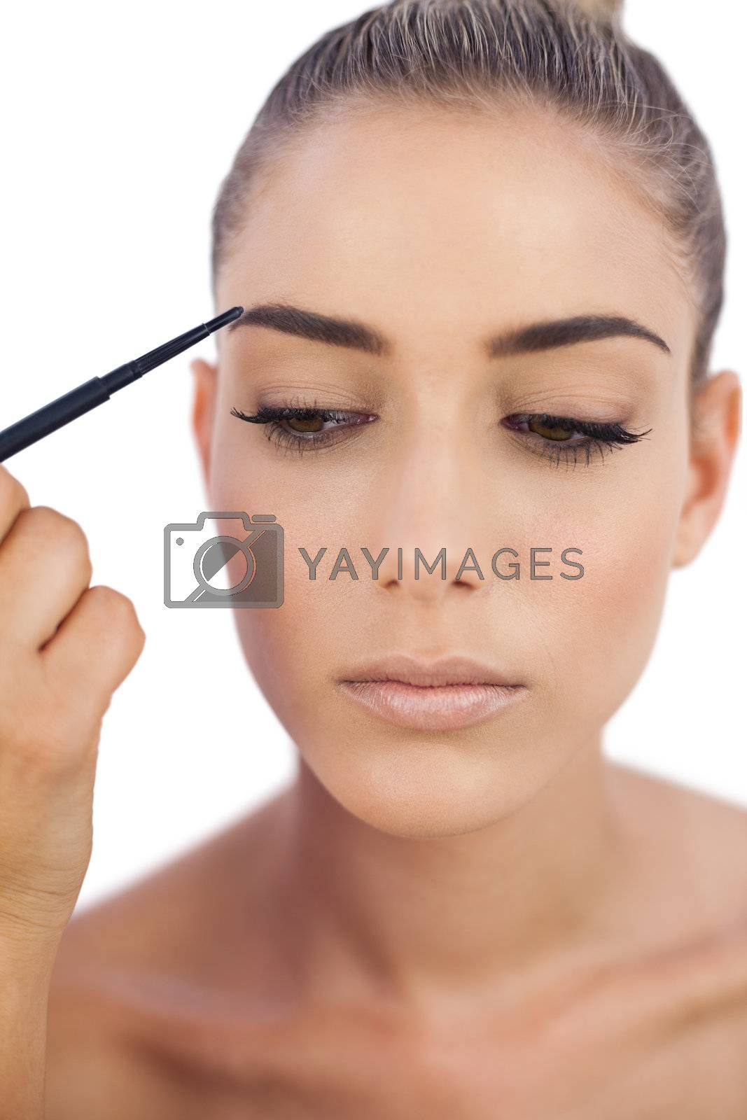 Thoughtful woman applying make up on her eyebrows by Wavebreakmedia