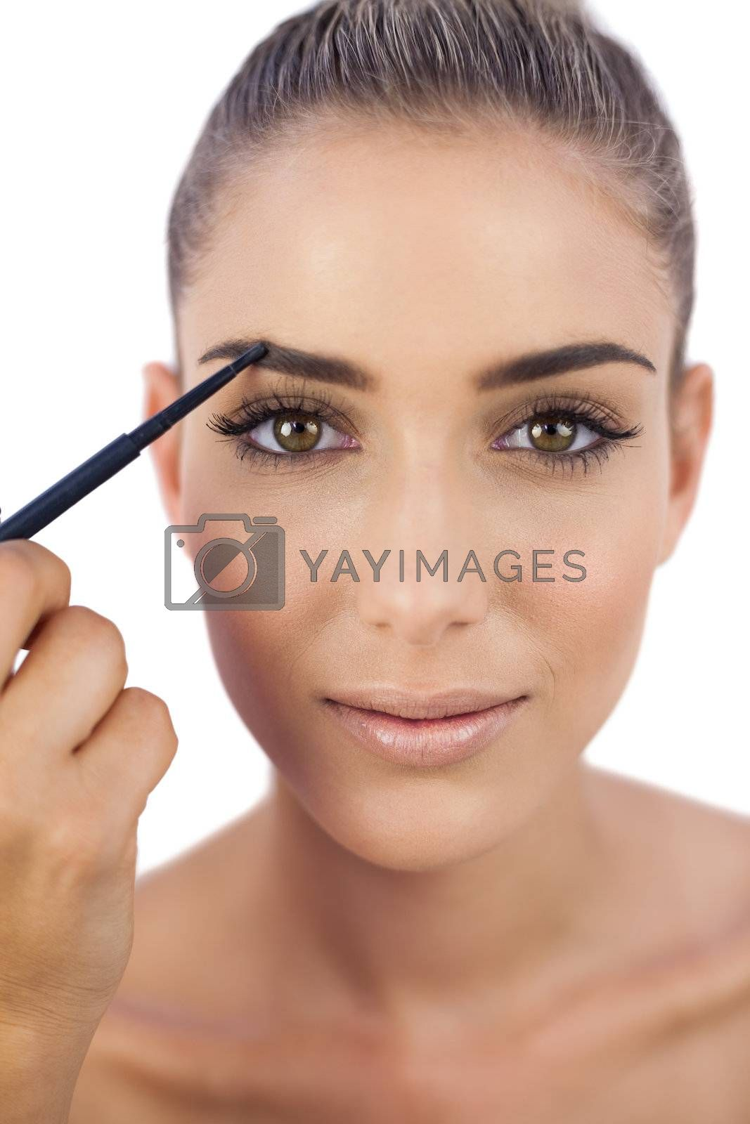 Content woman applying make up on her eyebrows by Wavebreakmedia