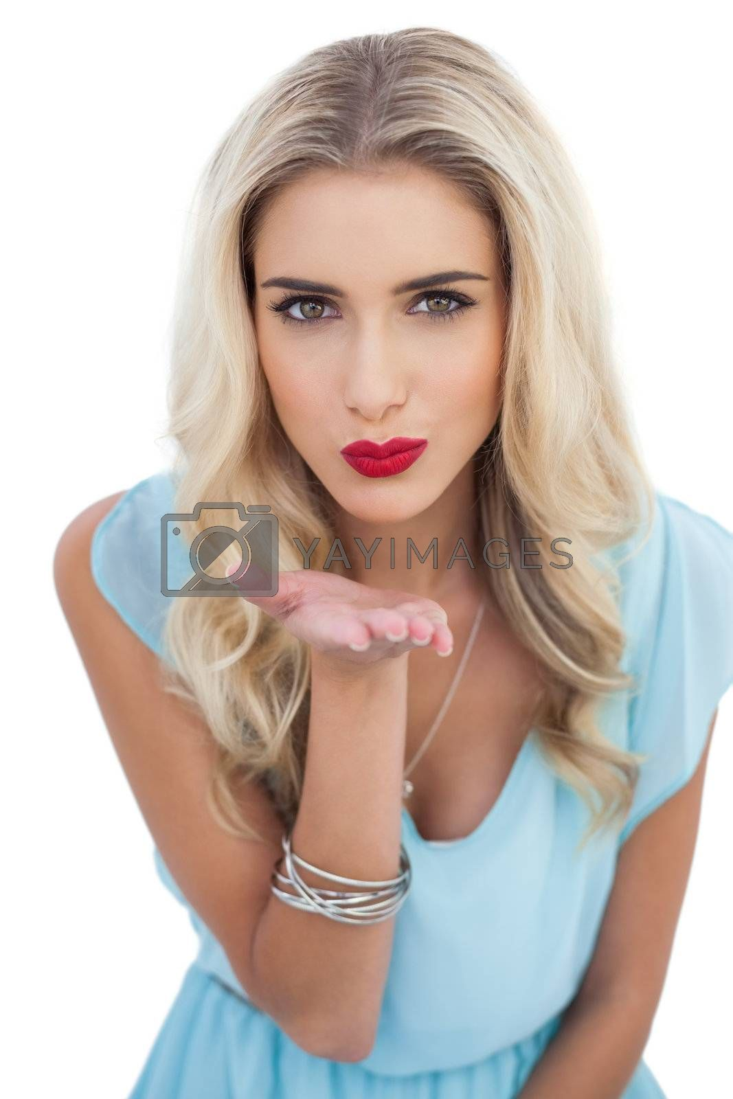 Seductive blonde model in blue dress sending a kiss to the camera by Wavebreakmedia