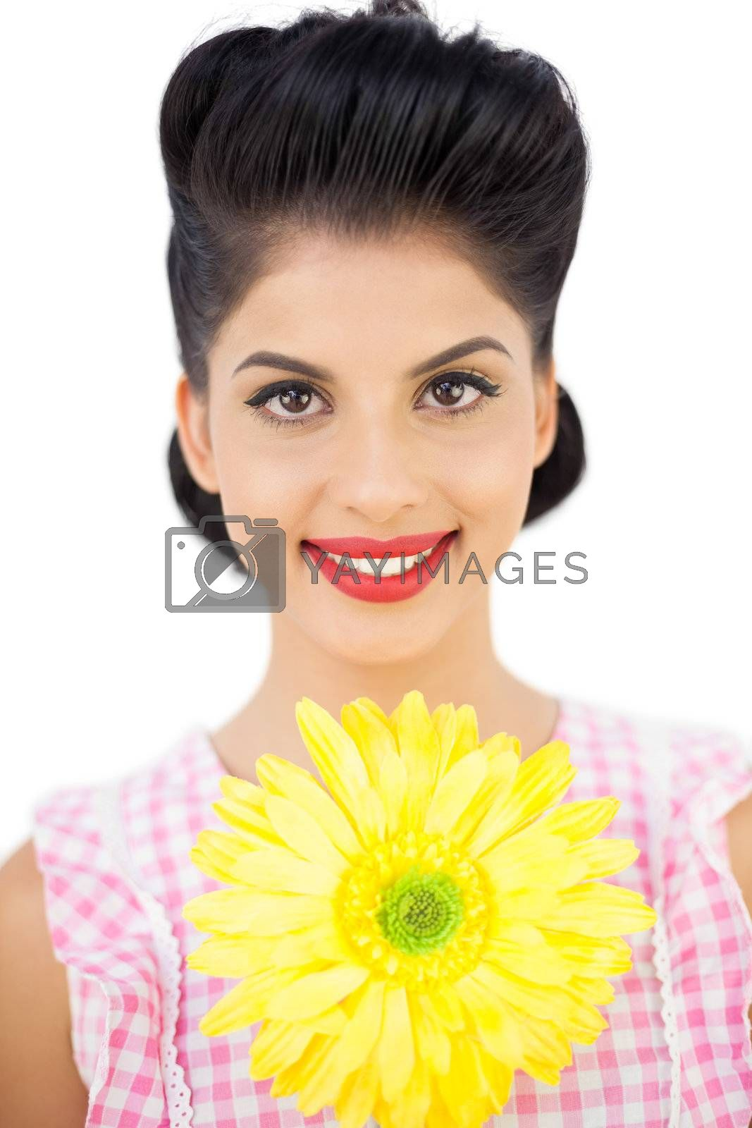 Smiling black hair woman showing a flower by Wavebreakmedia