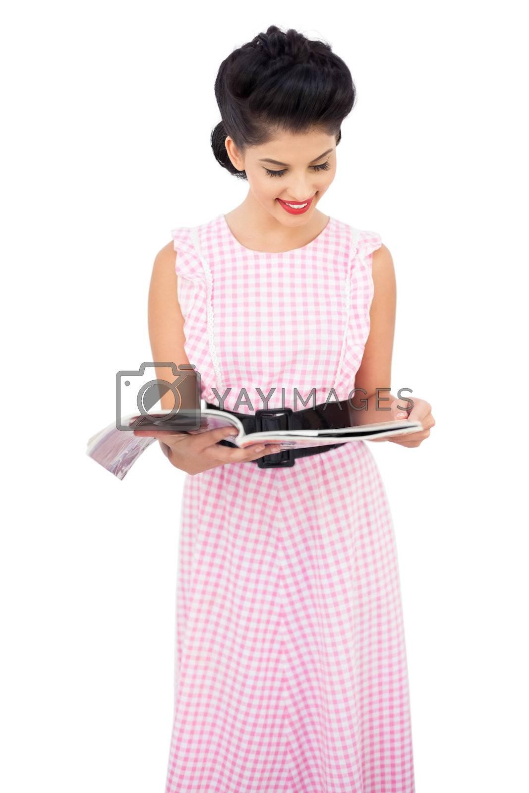 Pleased black hair model reading a magazine by Wavebreakmedia