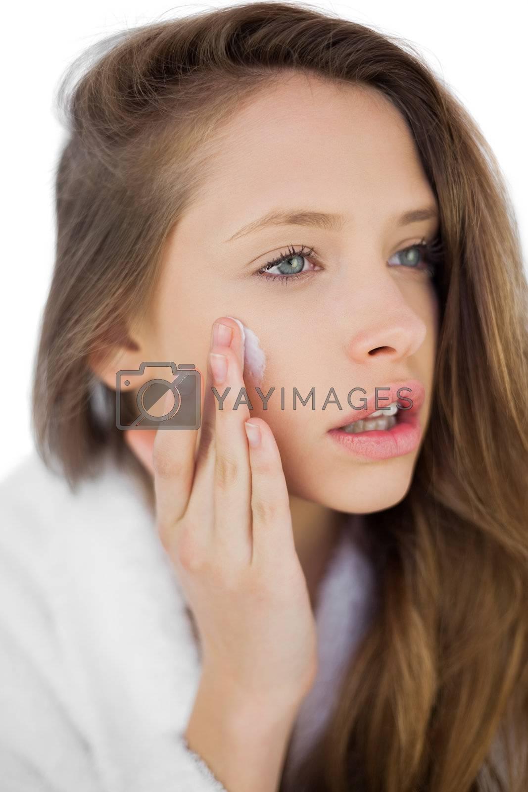 Thoughtful brunette in bathrobe rubbing her cheek with cream by Wavebreakmedia