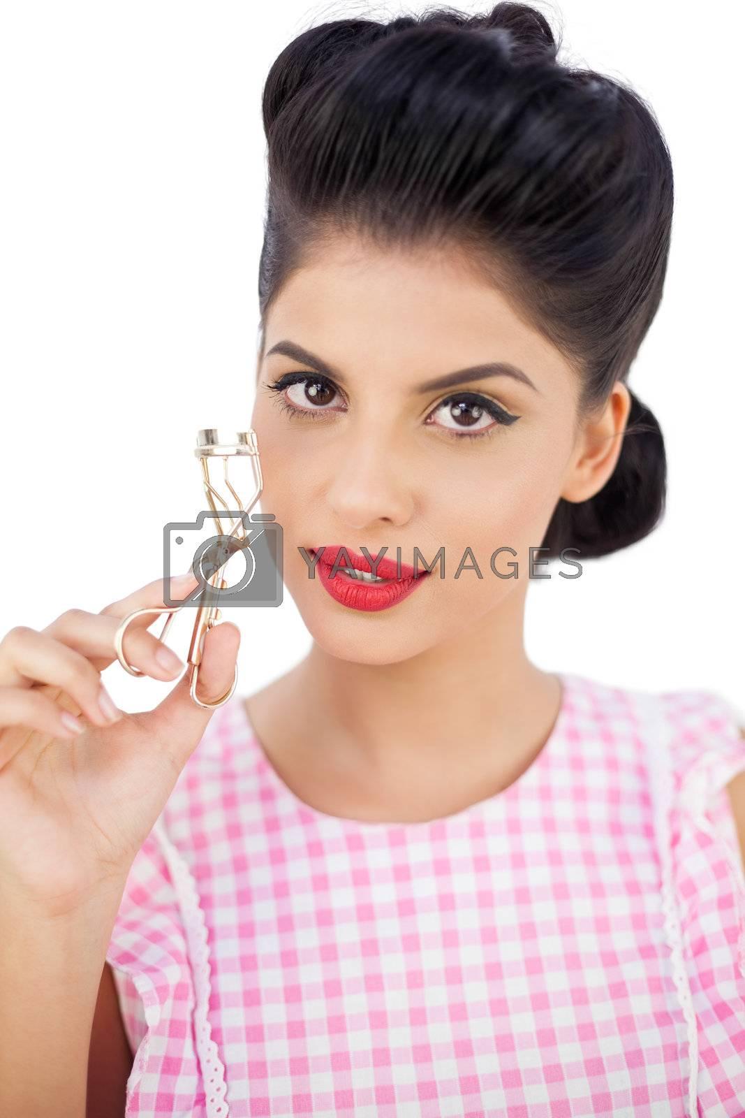Attractive black hair model holding an eyelash curler by Wavebreakmedia