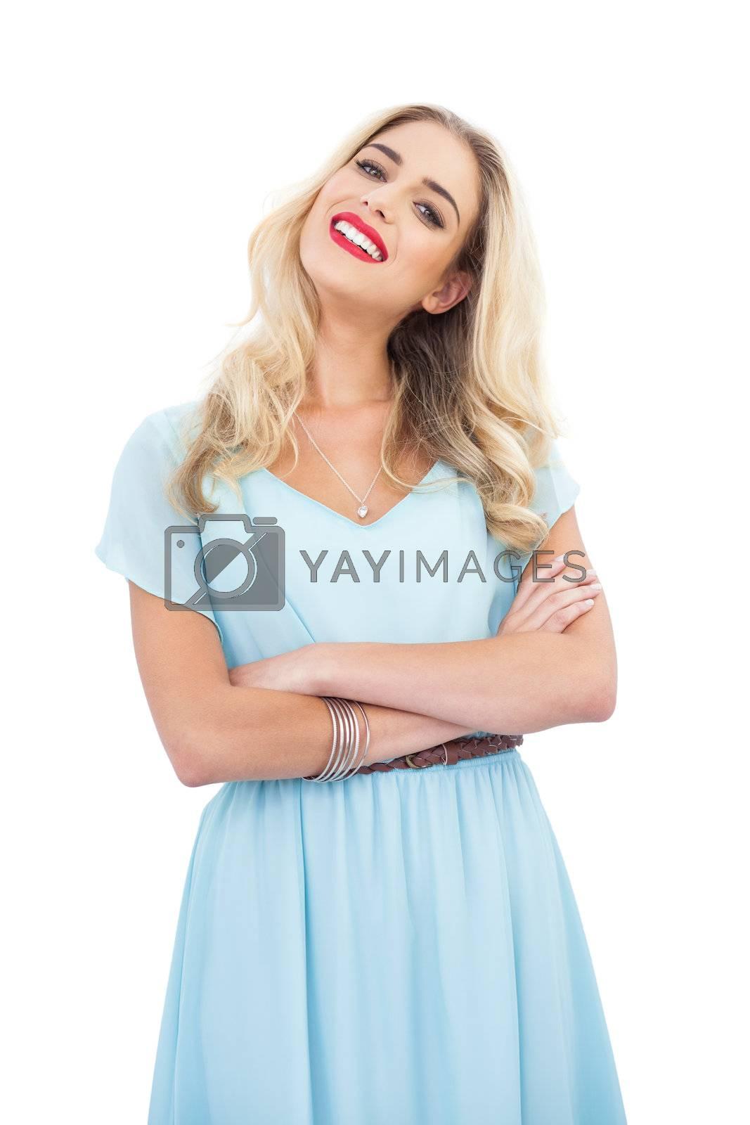 Content blonde model in blue dress posing crossed arms by Wavebreakmedia