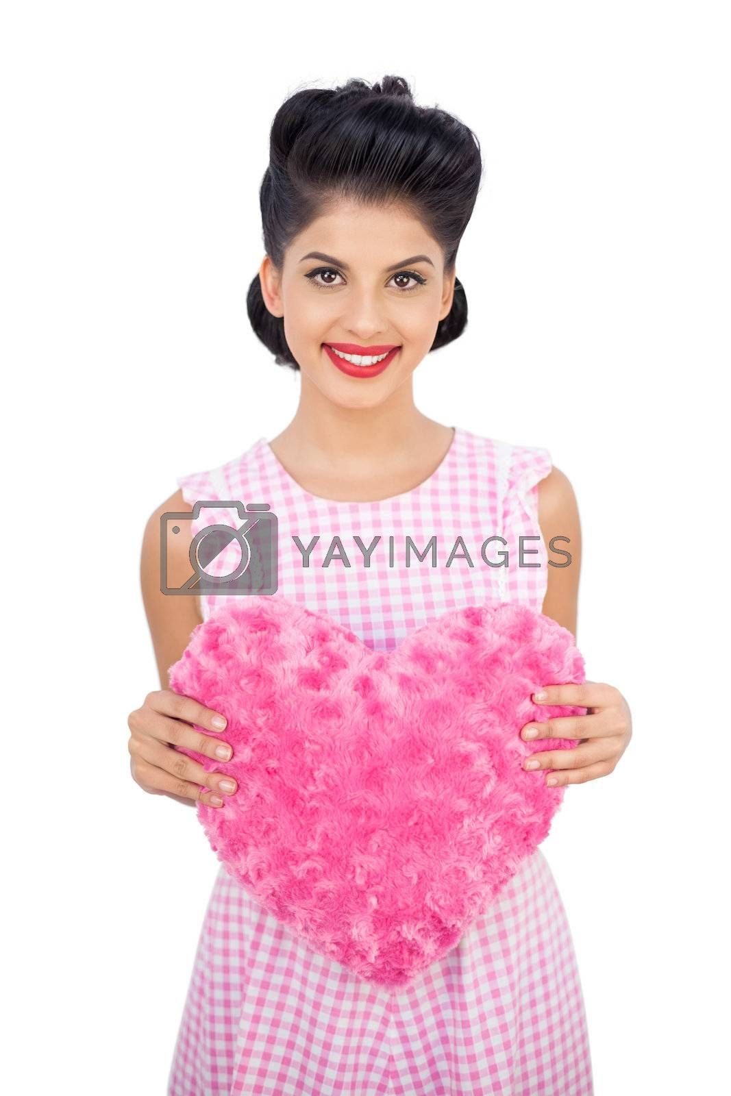 Delighted black hair model holding a pink heart shaped pillow by Wavebreakmedia