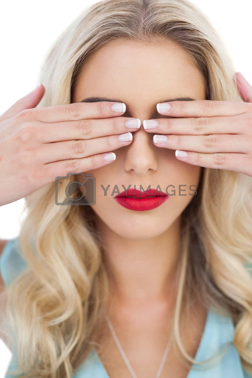 Blonde model in blue dress hidding her eyes with her hands by Wavebreakmedia