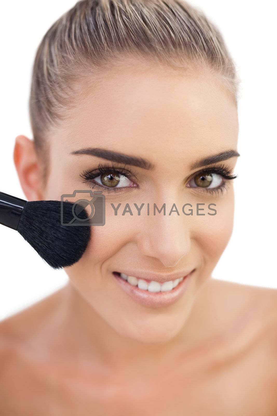 Cheerful woman applying powder on her cheeks by Wavebreakmedia
