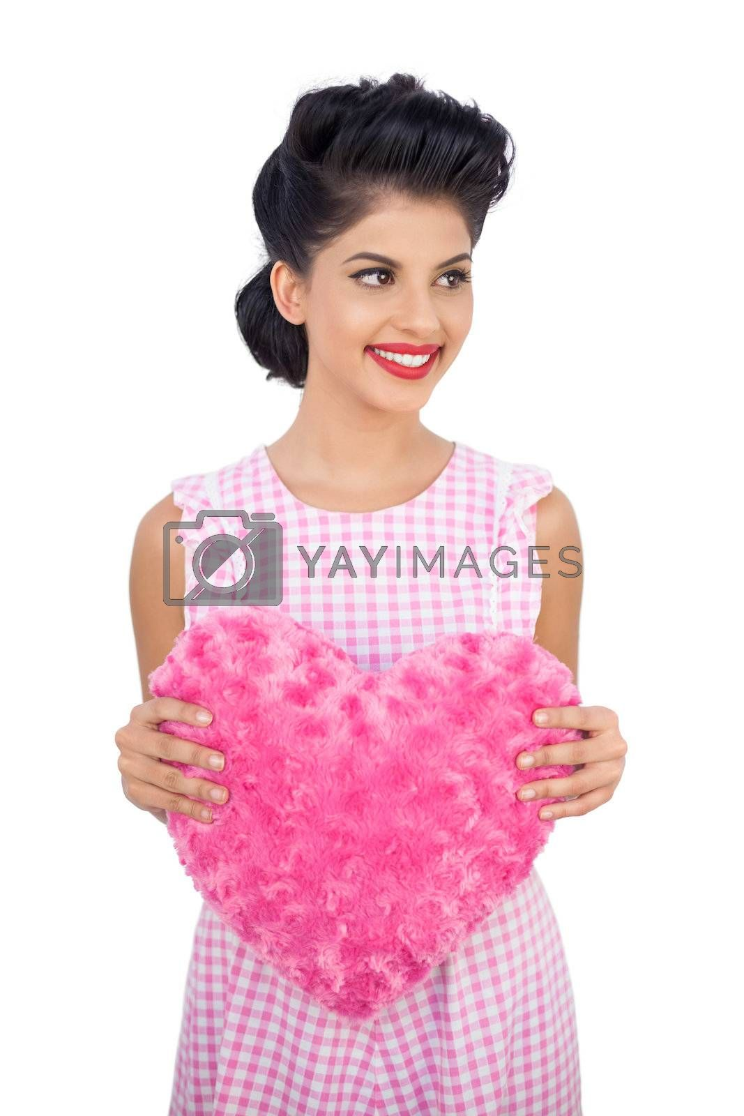 Cheerful black hair model holding a pink heart shaped pillow by Wavebreakmedia