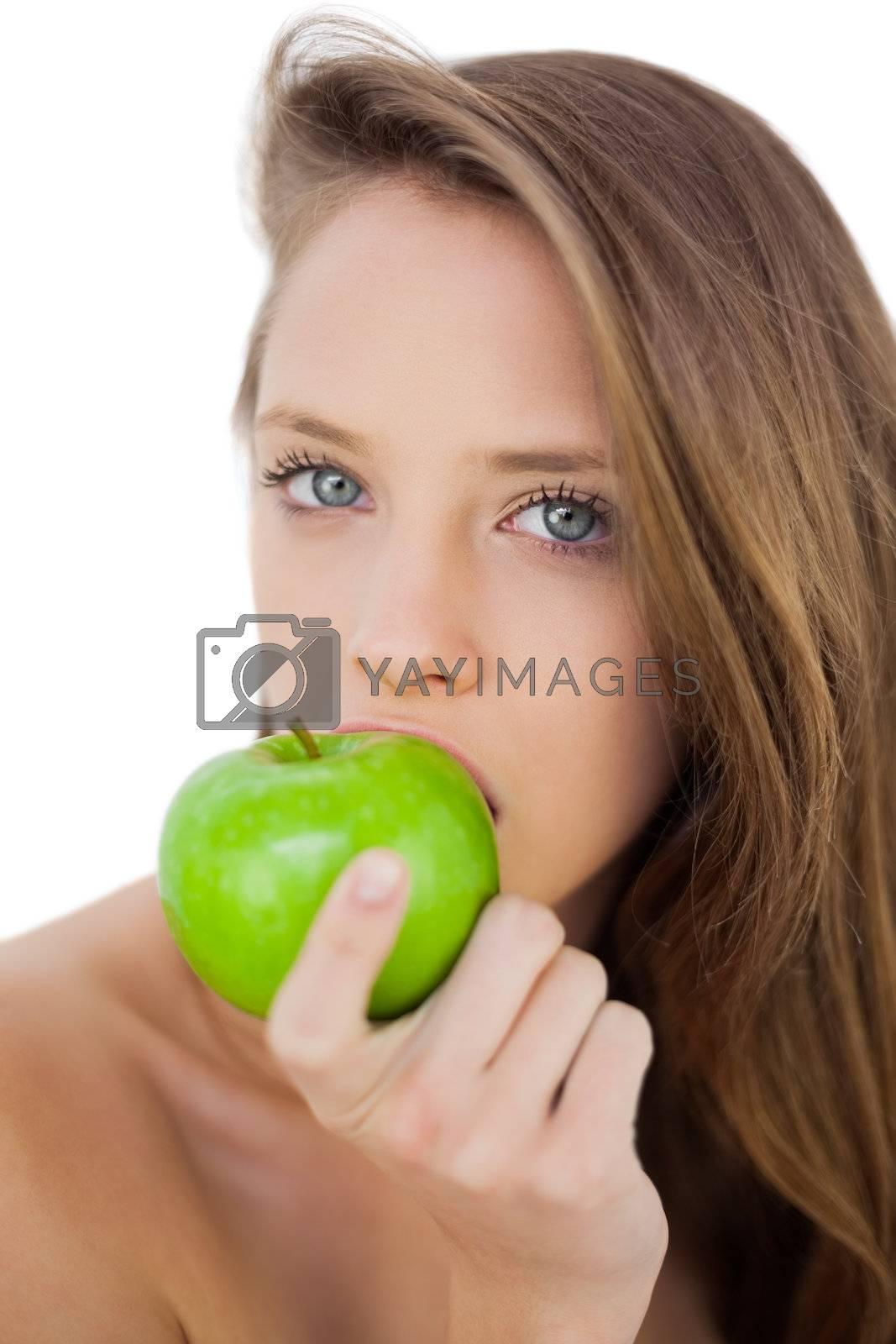 Serious brunette model eating an apple by Wavebreakmedia
