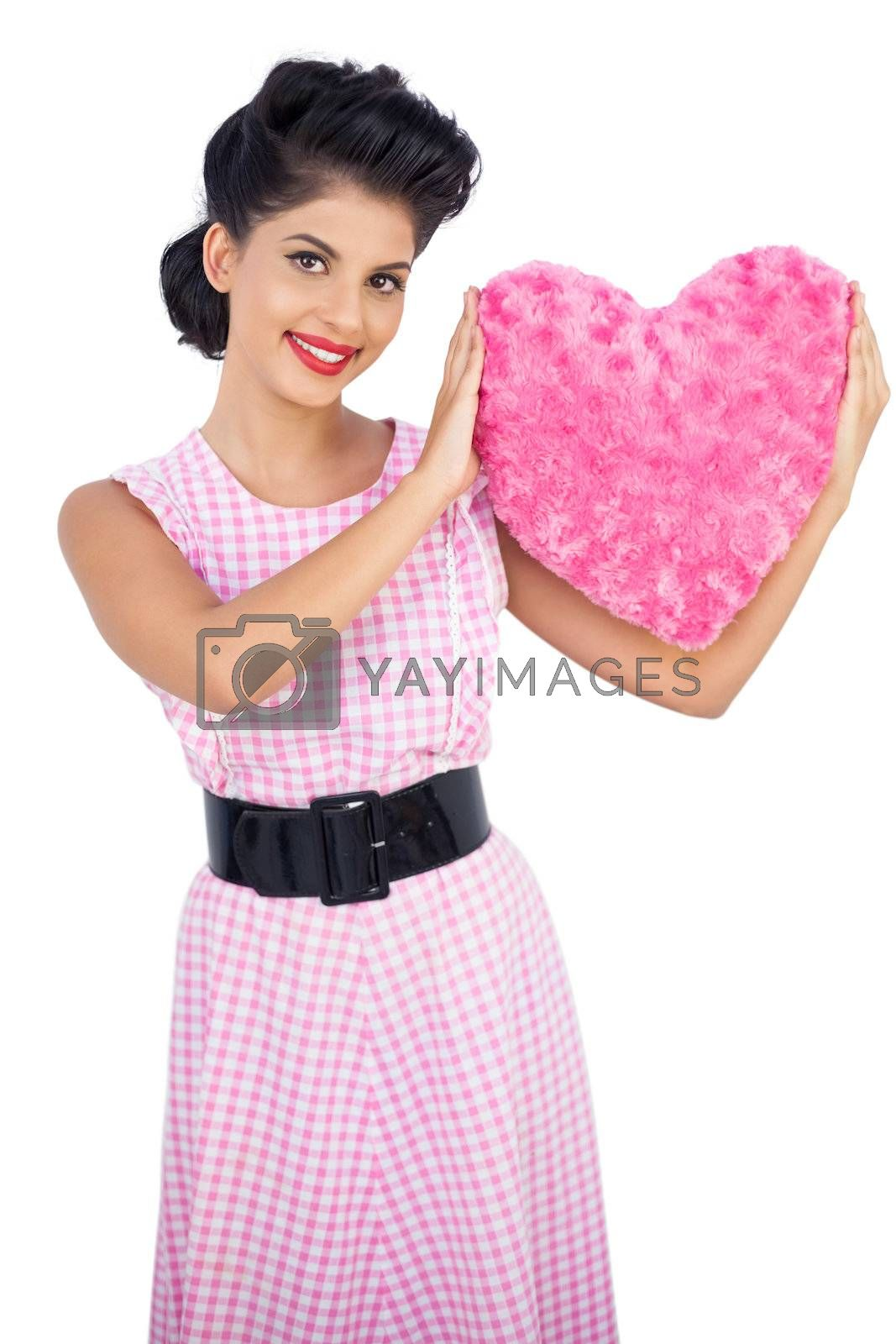 Playful black hair model holding a pink heart shaped pillow by Wavebreakmedia