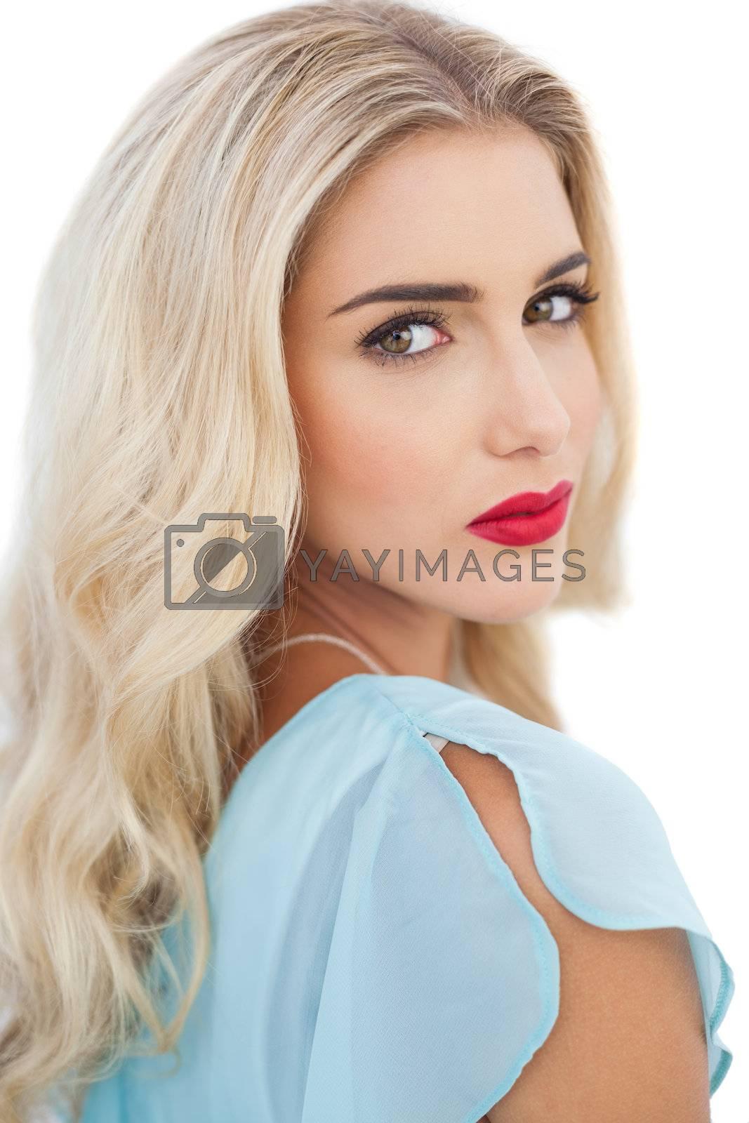 Portrait of a stylish blonde model in blue dress looking at camera by Wavebreakmedia