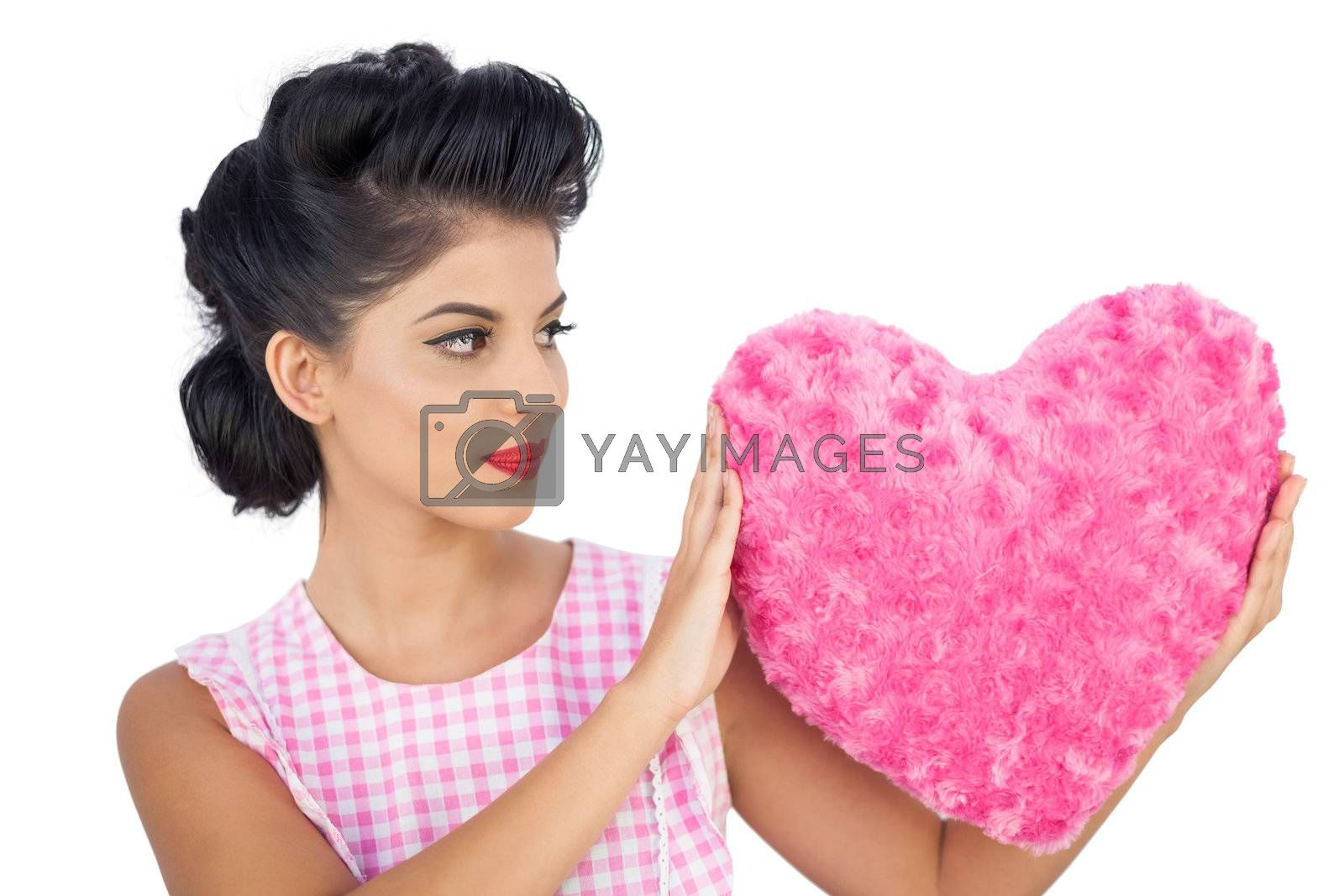 Charming black hair model holding a pink heart shaped pillow by Wavebreakmedia