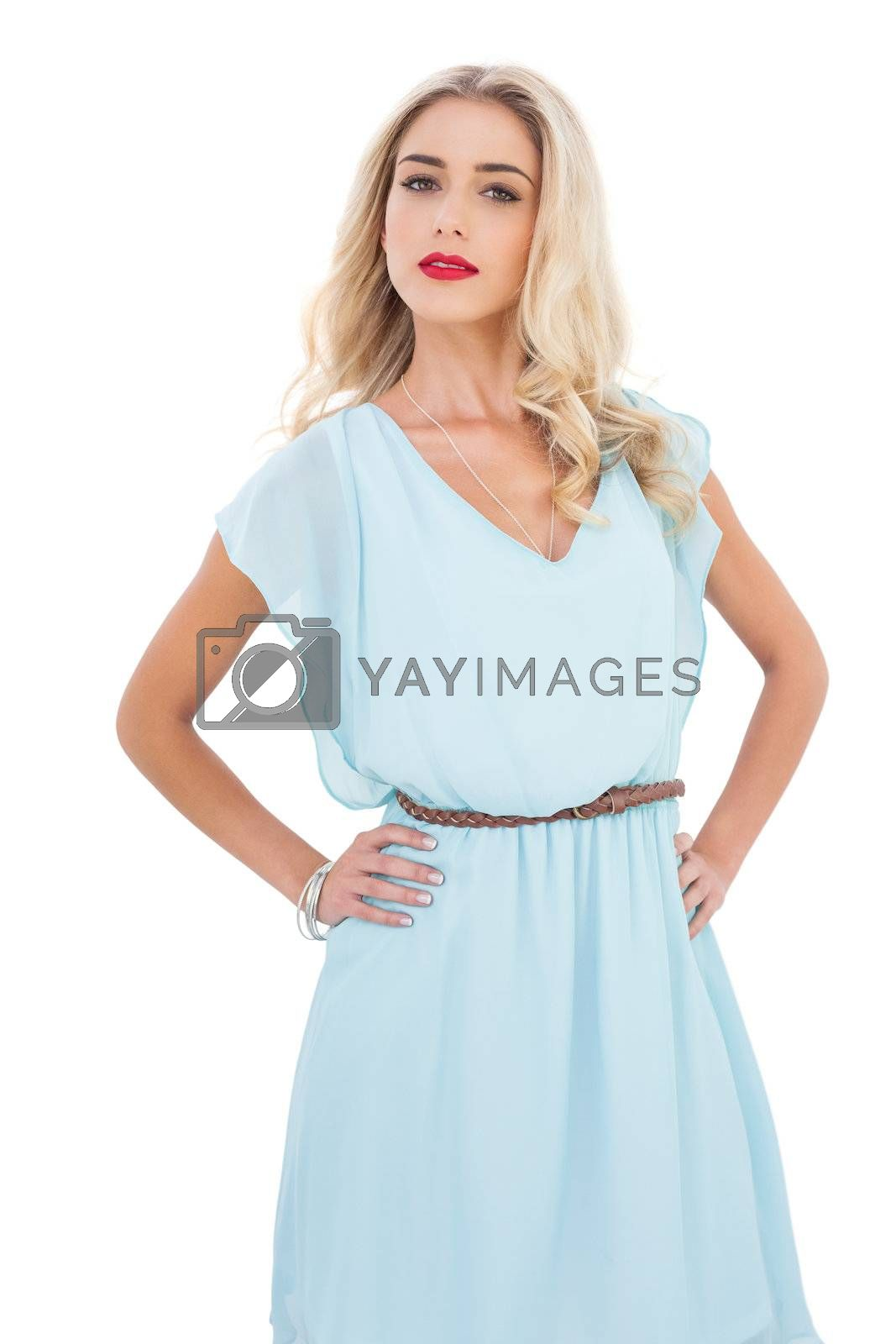 Gorgeous blonde model in blue dress posing hands on the hips by Wavebreakmedia