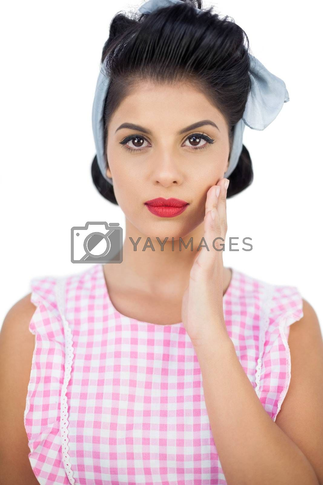 Serious black hair model posing with a hand on the cheek by Wavebreakmedia