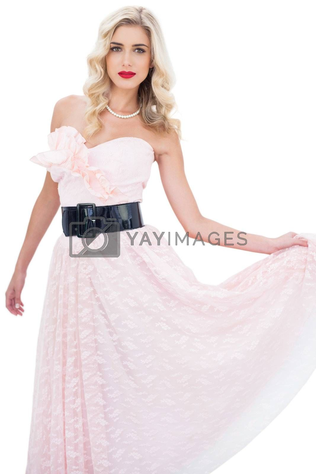 Stylish blonde model in pink dress posing holding her dress by Wavebreakmedia