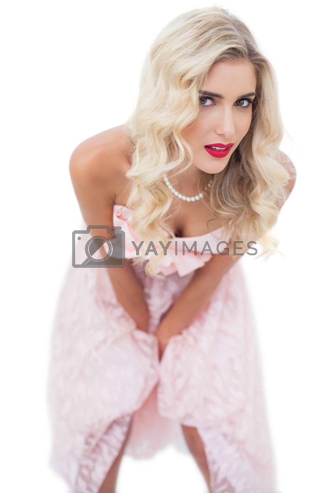 Dreamy blonde model in pink dress posing hands on the thighs by Wavebreakmedia