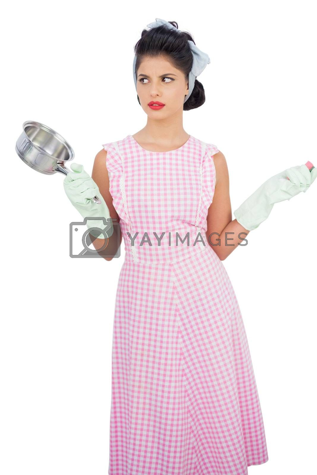 Puzzled black hair model holding a pan and wearing rubber gloves  by Wavebreakmedia