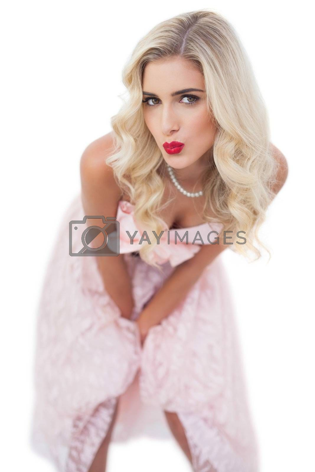 Cute blonde model in pink dress posing hands on the thighs by Wavebreakmedia