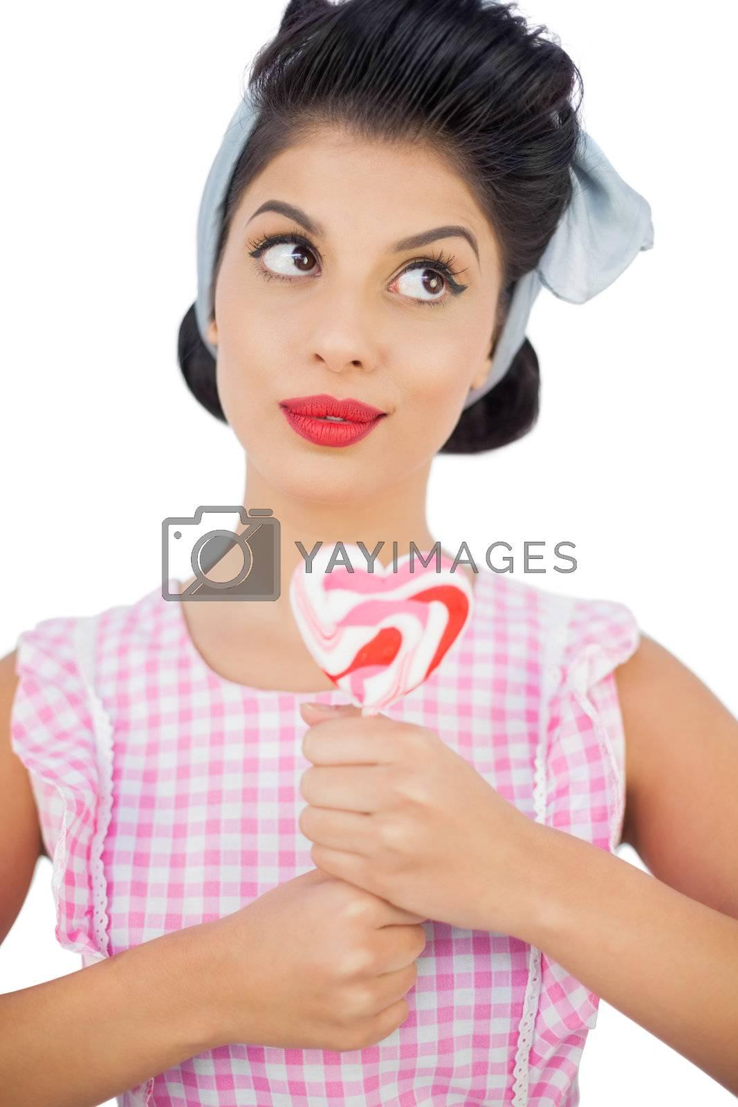 Pensive black hair model holding a heart shaped lollipop by Wavebreakmedia