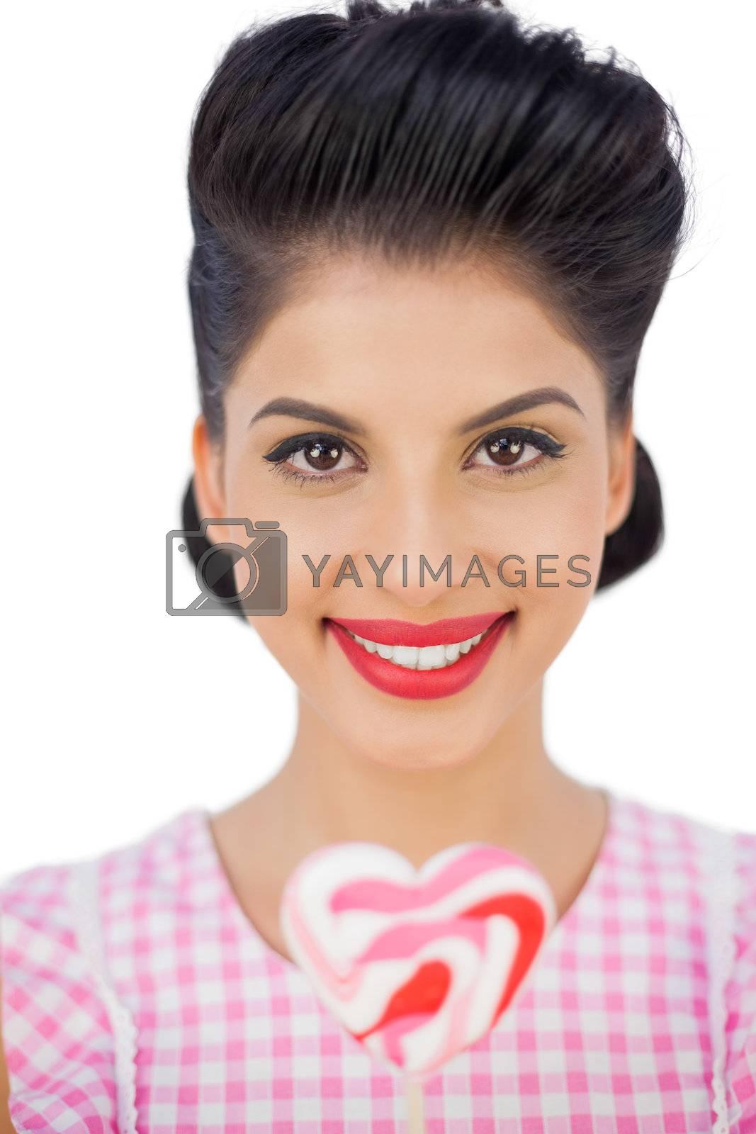 Happy black hair model holding a heart shaped lollipop by Wavebreakmedia