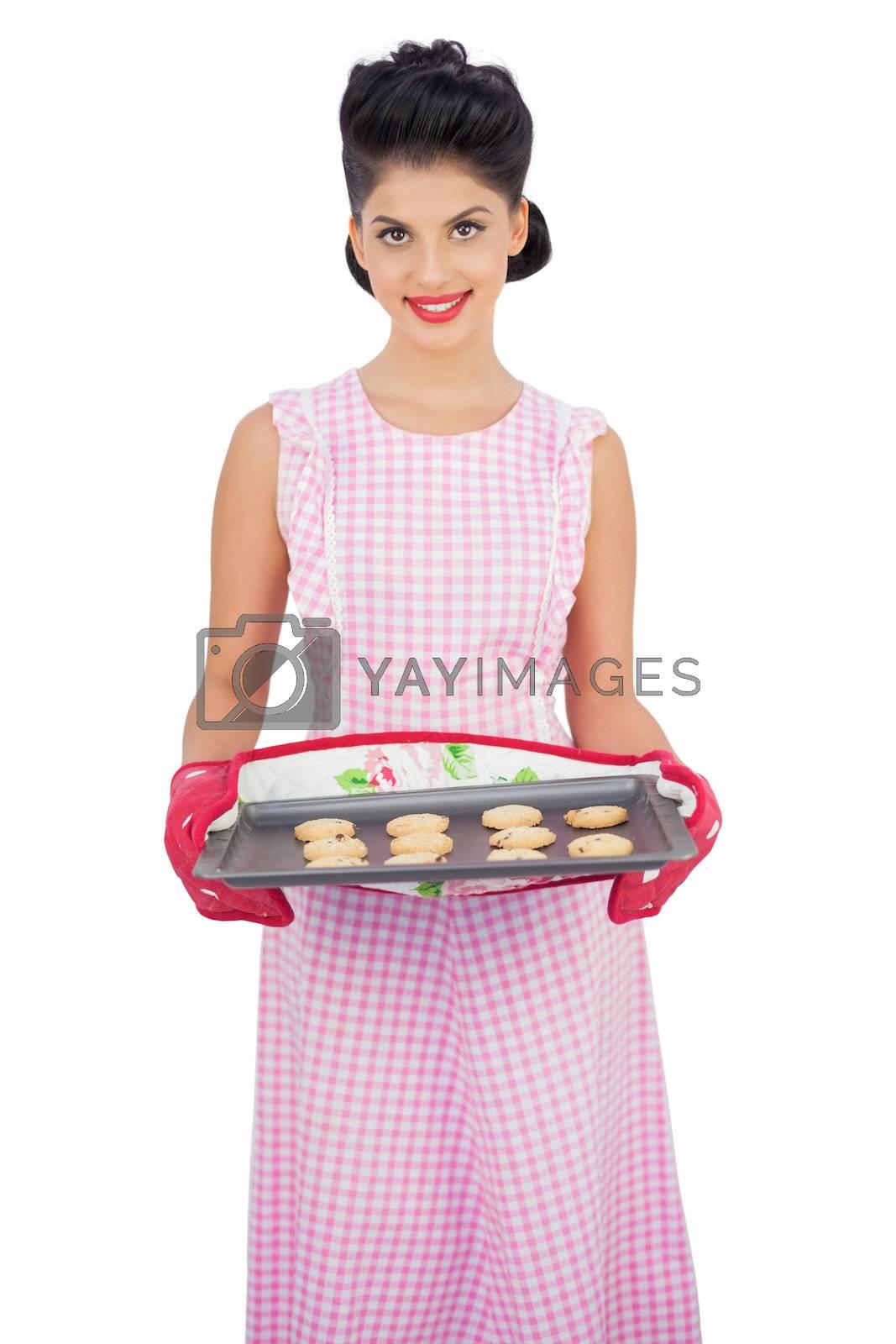 Pleased black hair model holding a baking tray of cookies by Wavebreakmedia