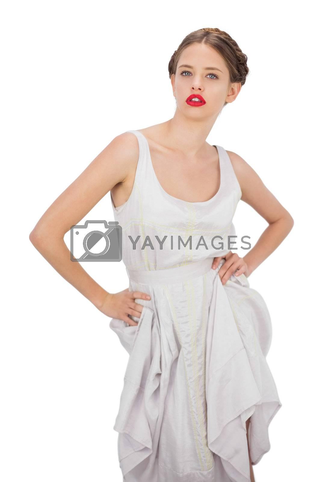 Severe model in white dress posing hands on the hips by Wavebreakmedia