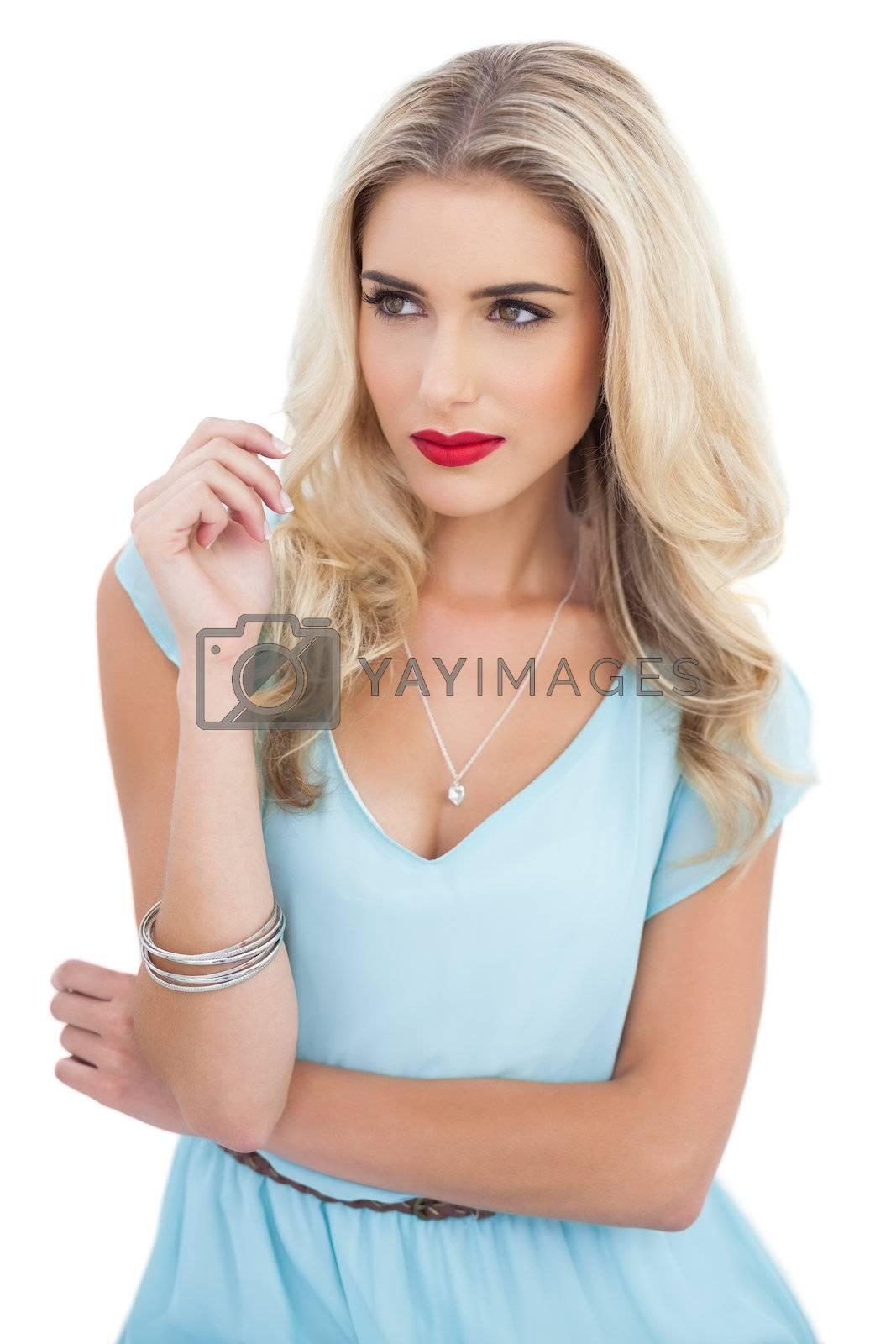 Attractive blonde model in blue dress looking away by Wavebreakmedia